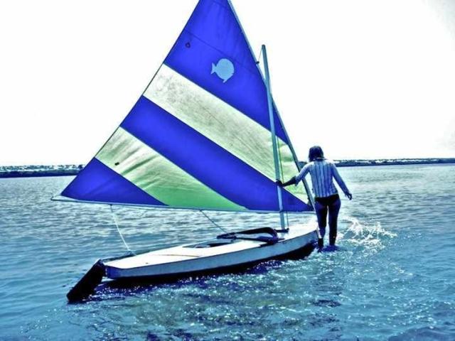 Walking a sunfish over a sandbar in salt run the summer a taught youth sailing.